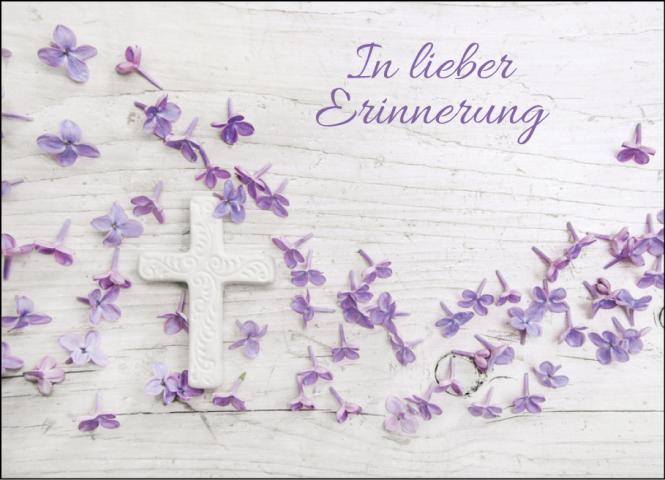 Steinkreuz mit lila Blüten